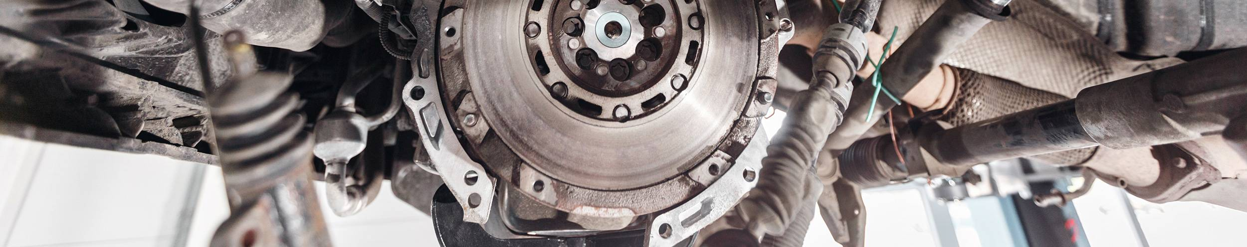 close up of clutch disk underneath car in garage