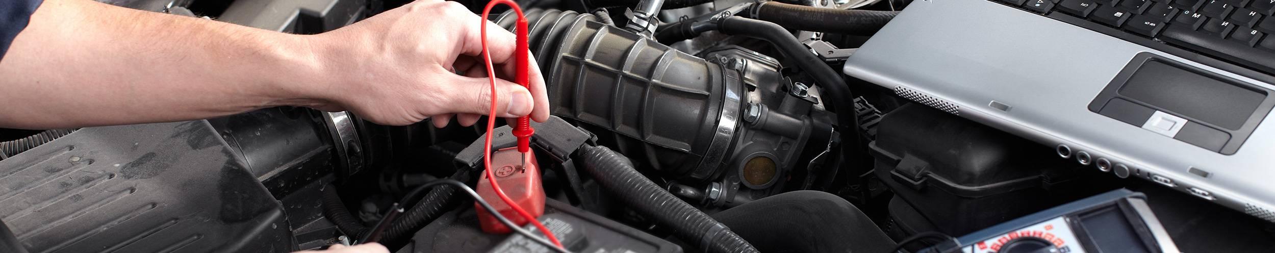 mechanic performing car engine diagnostics with laptop